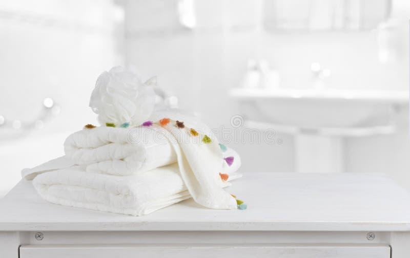 在木逆桌上的白色棉花毛巾在明亮的卫生间里面 库存照片
