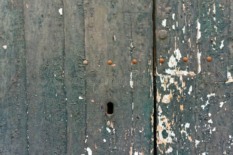 在木门和关键孔的老剥落的油漆 库存照片