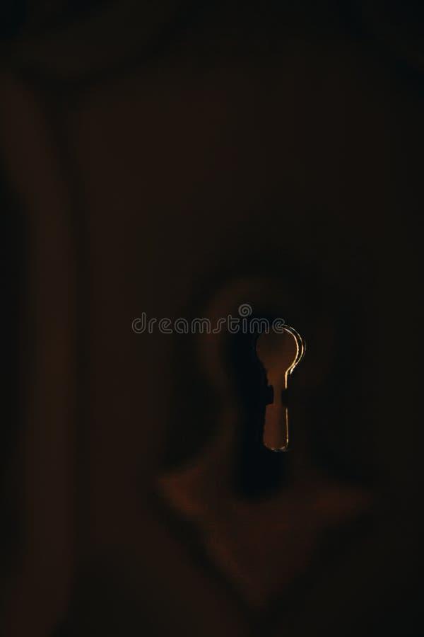 在木门特写镜头宏指令的老葡萄酒金属匙孔 有锁槽孔的板材 图库摄影