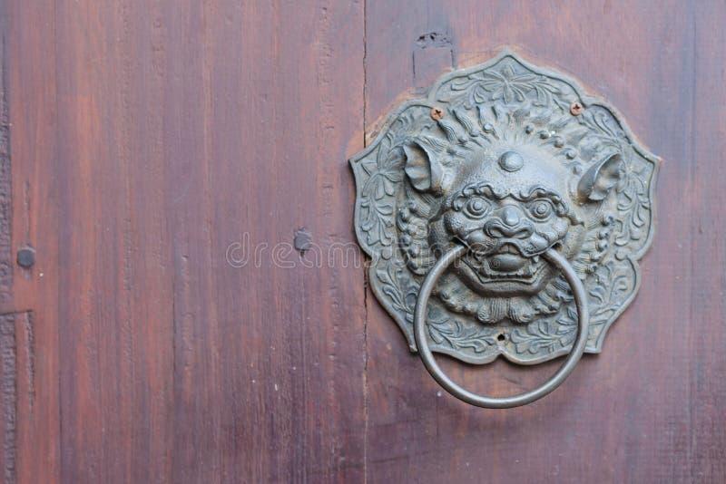 在木门的古色古香的中国狮子把柄与拷贝空间 免版税库存图片