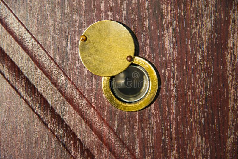 在木门的窥视孔- judas钻孔窥视孔 免版税库存照片