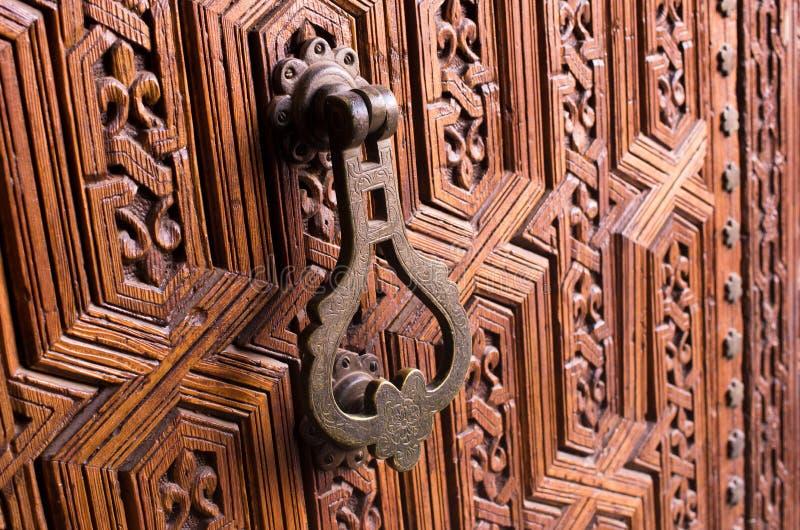 在木门的老敲门人 免版税库存图片
