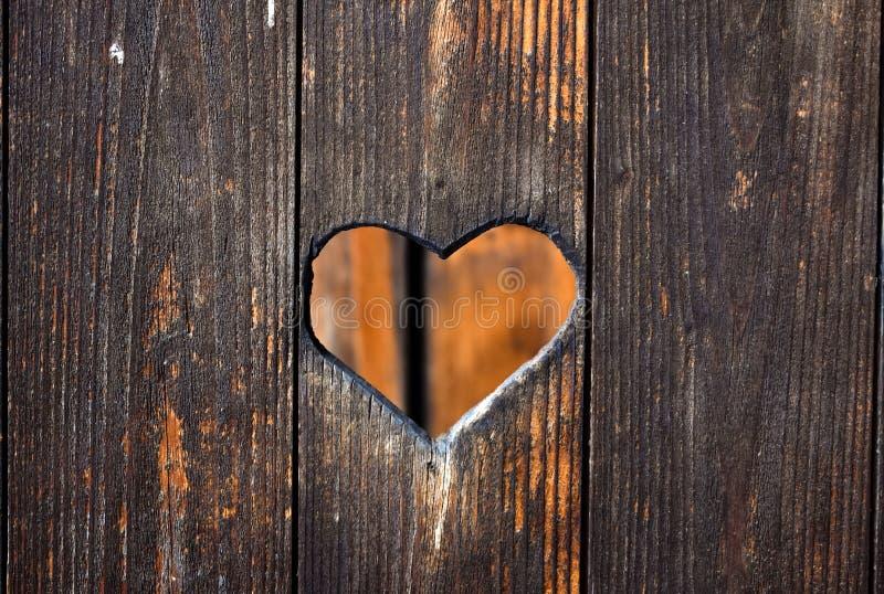 在木门雕刻的心脏形状 免版税库存图片
