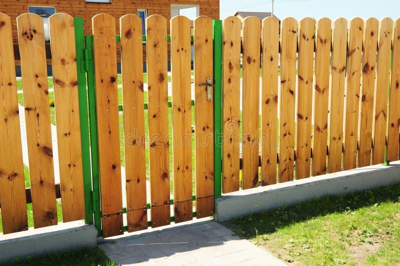 在木门(小门)的特写镜头和有室外的门道入口的木篱芭细节建筑 库存照片