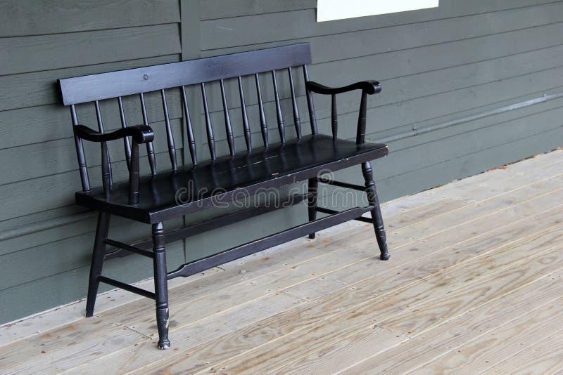 在木门廊的老黑长凳 库存照片
