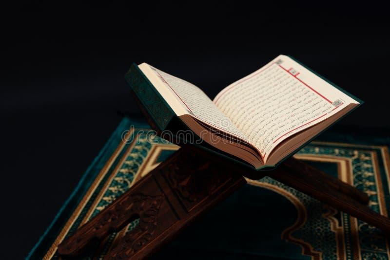 在木雕刻的rahle的伊斯兰教的圣经古兰经与念珠小珠和在黑背景的跪毯 r 免版税库存照片