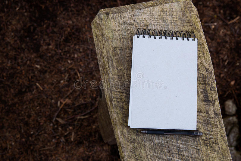 在木头和森林纹理背景的笔记薄  图库摄影