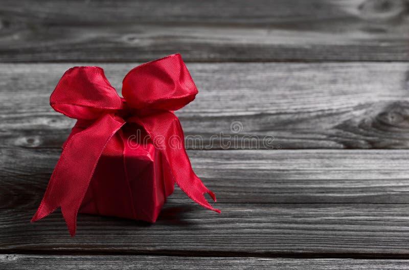 在木破旧的背景的一个红色欢乐圣诞节礼物 免版税库存图片