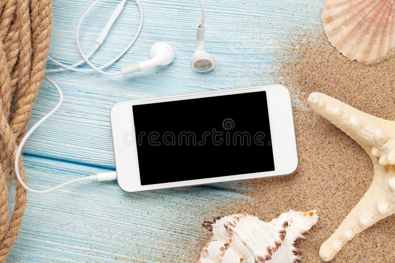 在木头的与海星和壳的智能手机和海沙 免版税库存照片