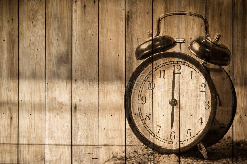 在木头的减速火箭的时钟葡萄酒样式 库存照片