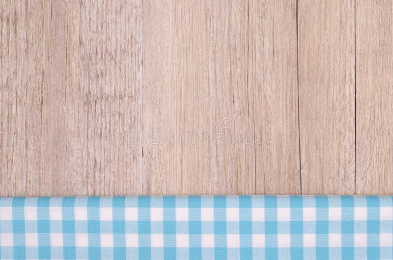 在木头的浅兰的方格的布料 免版税库存照片