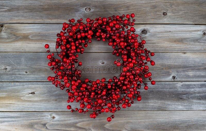在木头的红色莓果假日花圈 库存图片