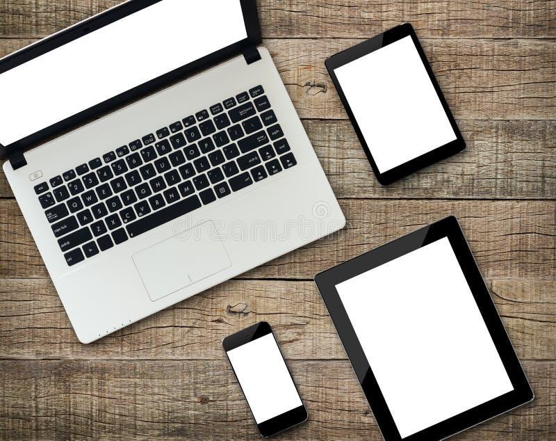 在木头的通信装置现代设备白色屏幕显示 免版税库存照片