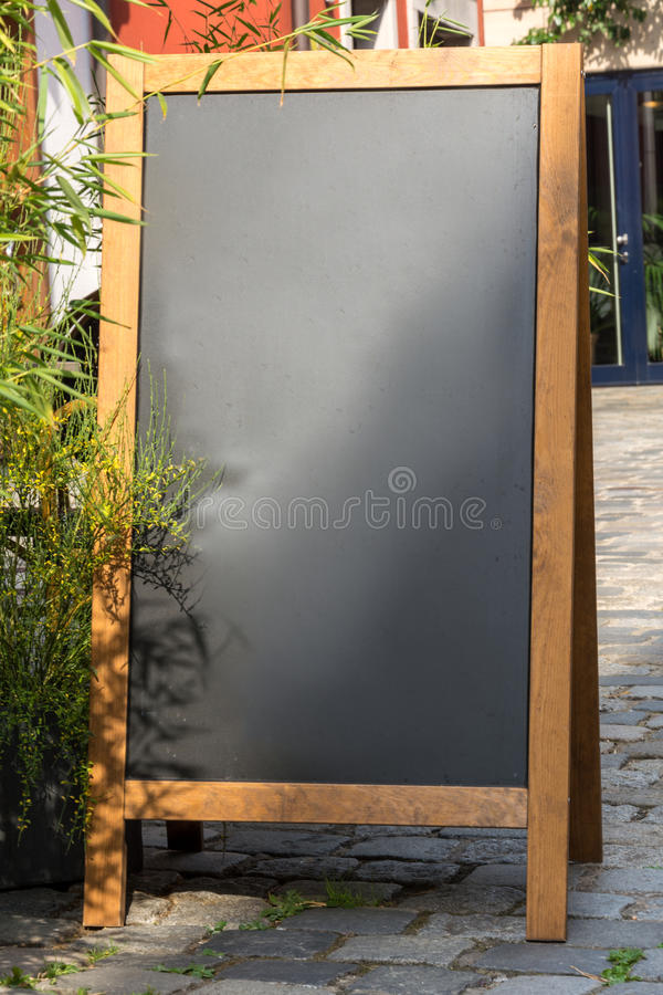 在木头的黑黑板立场在stre的一份餐馆菜单的 免版税库存照片