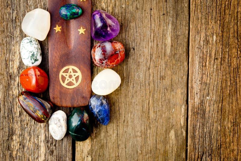在木头附近的水晶石头与黄铜五角星形标志 免版税库存图片