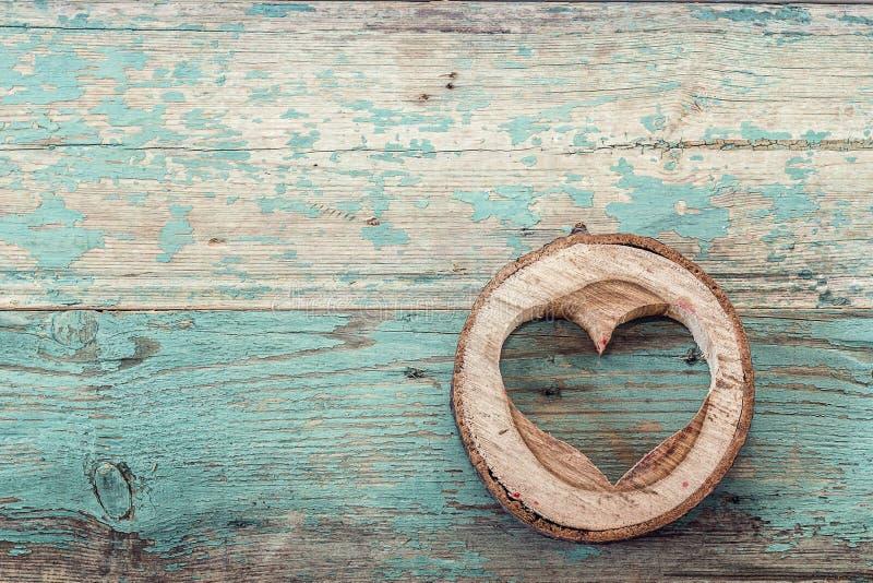 在木头雕刻的心脏形状在老绿松石板切开了 图库摄影