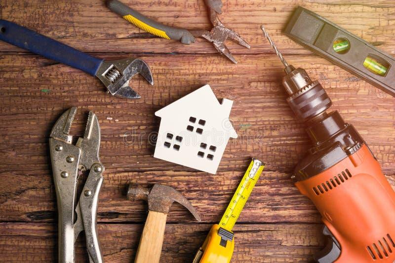 在木backgrou的木白色房子玩具和建筑工具 库存照片