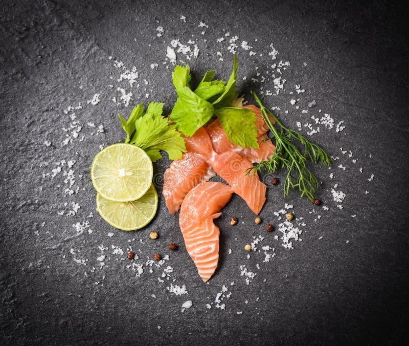 在未加工的三文鱼生鱼片海鲜黑色的盘子背景顶视图的三文鱼沙拉/鱼三文鱼内圆角用柠檬草本和香料 免版税库存照片