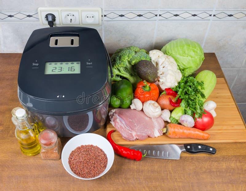 在未加工的食物中的电多烹饪器材在厨师桌上 免版税库存照片