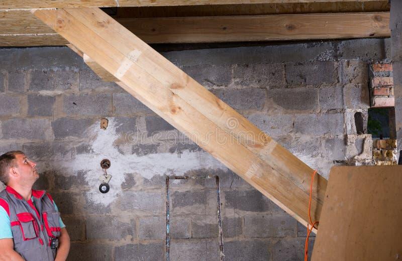 在未完成的家庭检查的楼梯的建造者 免版税库存图片