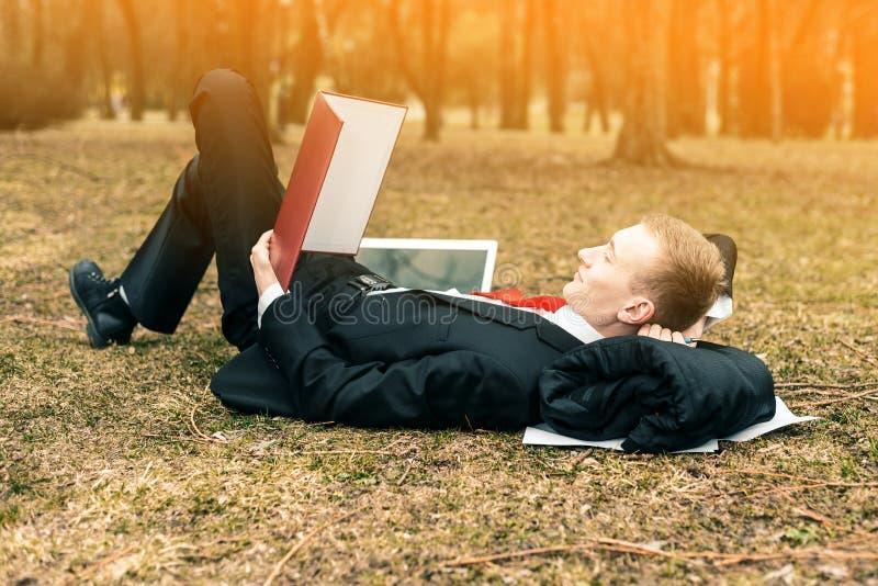 在本质上与膝上型计算机的年轻人 工作的商人遥远地户外 自由职业者读文件 库存照片