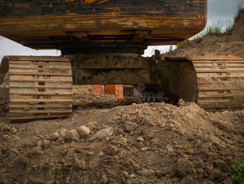 在机器的领域、肮脏的轨道和被抓的边的老使用的挖掘机在棕色土壤的 概念坚硬实际工作 图库摄影