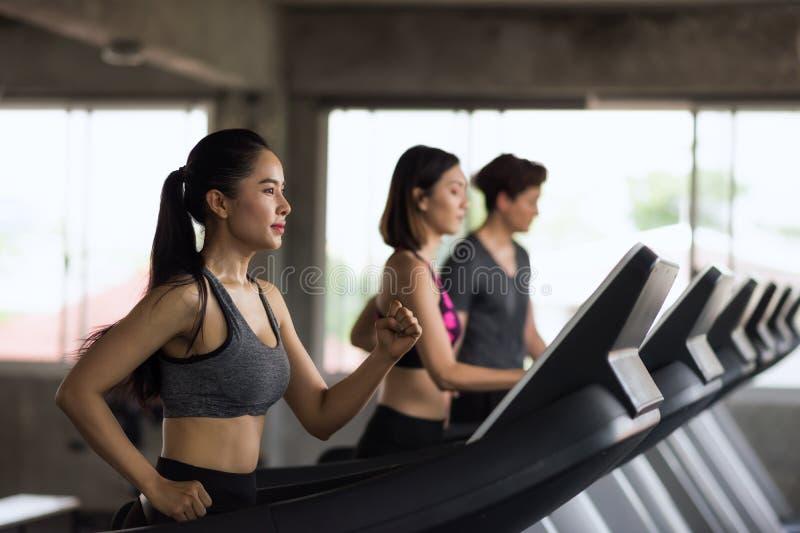 在机器跑的年轻亚裔朋友在健身房 免版税库存照片