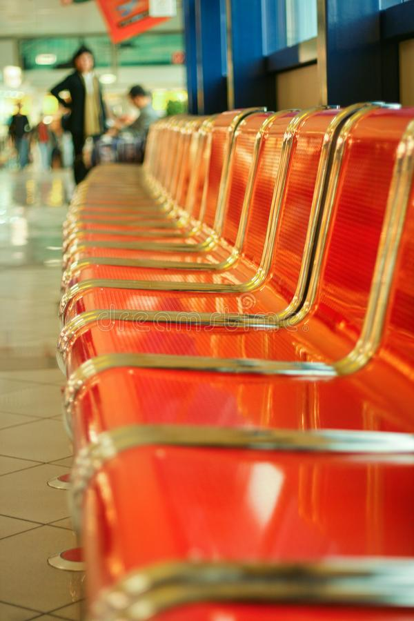 在机场大厅的空的红色金属位子 免版税库存图片