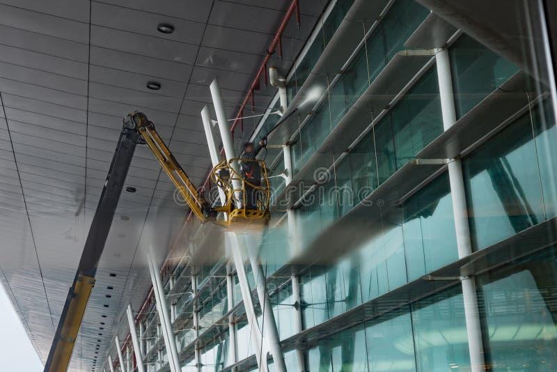 在机场大厅的风窗清洁器,站立在起重机 免版税图库摄影