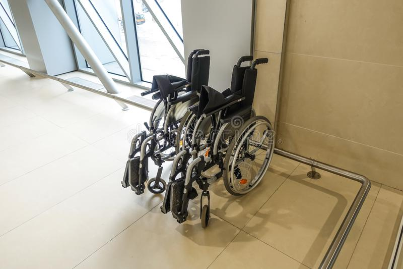 在机场大厦的轮椅 照料人以伤残 免版税图库摄影
