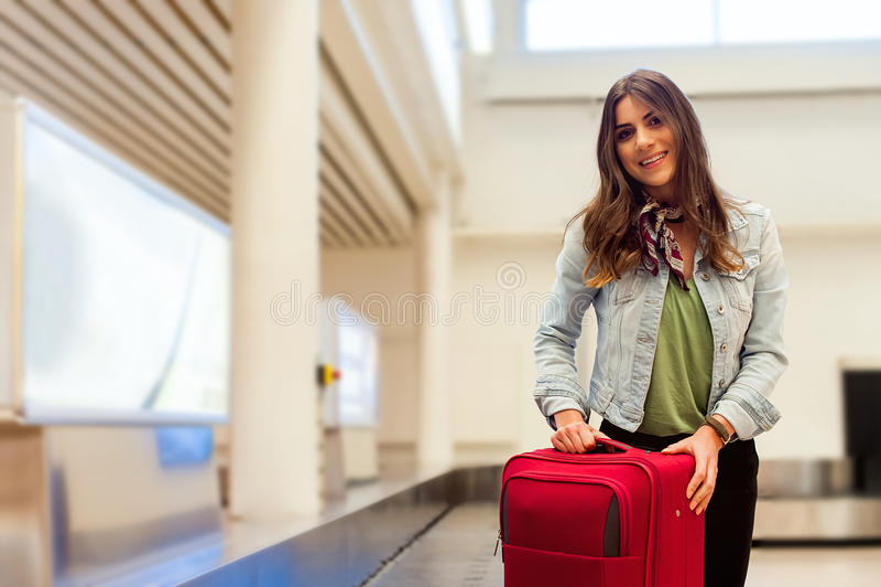 在机场收集她的行李的妇女在传送带区域 库存照片