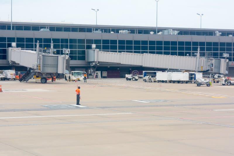 在机场穿戴一件红色安全夹克的工作者 库存图片
