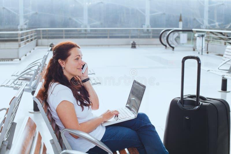 在机场谈话由电话和检查在膝上型计算机,商务旅游的妇女电子邮件 免版税库存照片