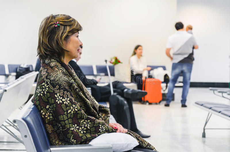 在机场` s离开休息室供以座位的妇女等待 免版税库存照片