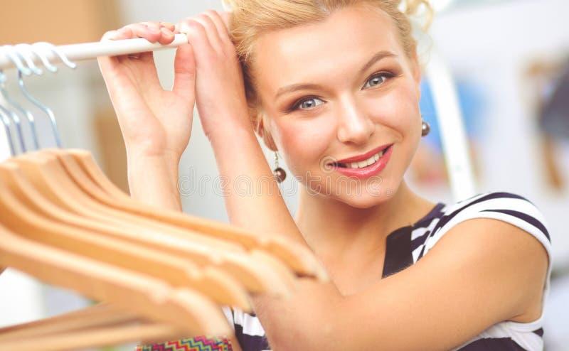 在机架附近的美丽的年轻美发师有挂衣架的在办公室 免版税图库摄影