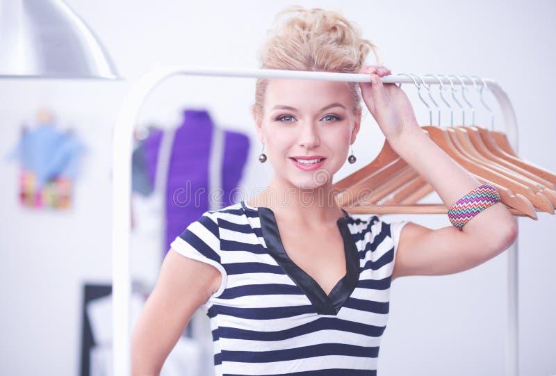 在机架附近的美丽的年轻美发师有挂衣架的在办公室 免版税库存图片