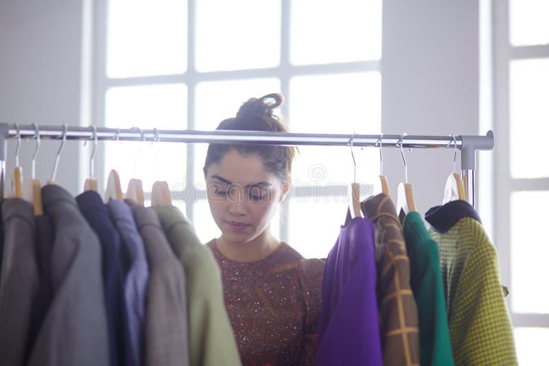 在机架附近的美丽的年轻美发师藏品剪贴板有在白色背景的名牌服装的 图库摄影