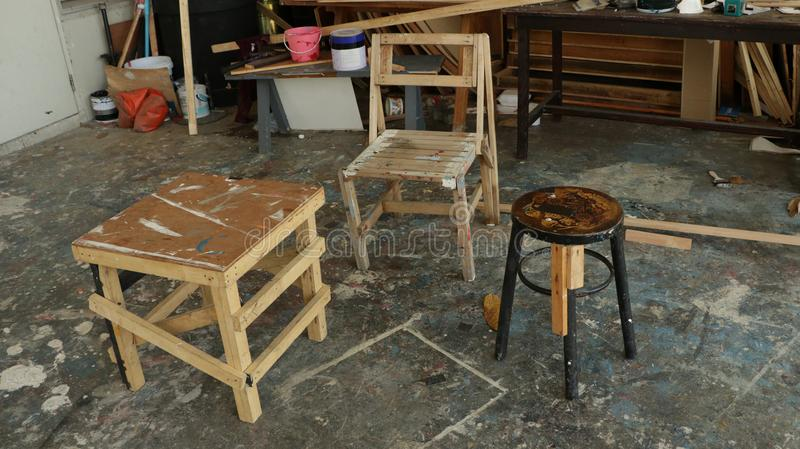 在杂乱仓库前面的肮脏的木椅子 免版税库存照片