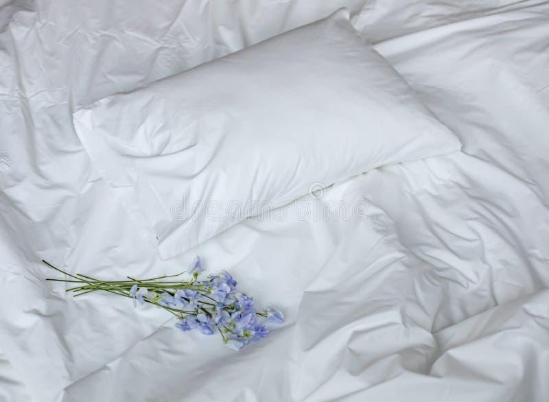 在杂乱床、白色卧具项目和蓝色花bouqet上的花 免版税库存照片