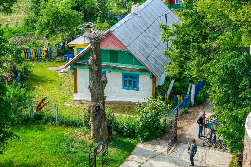 在杆和colorfulled老木房子的鹳巢 免版税库存照片