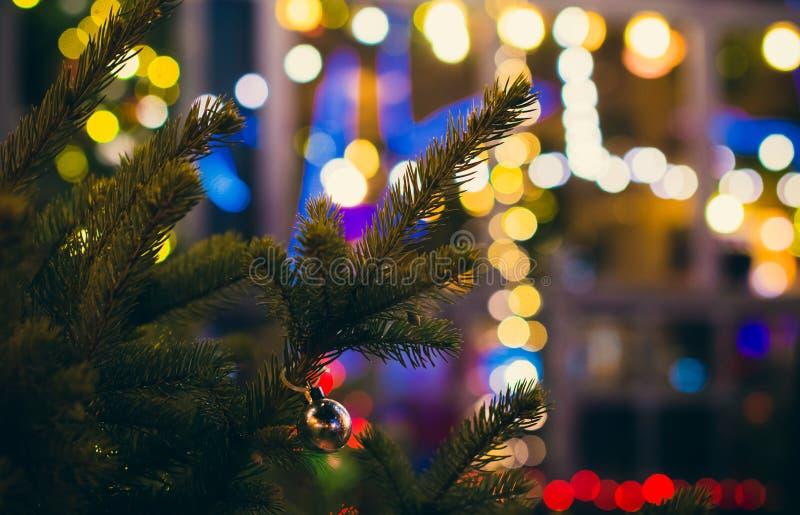 在杉木的小银色玻璃球圣诞装饰在街道上在晚上 库存照片