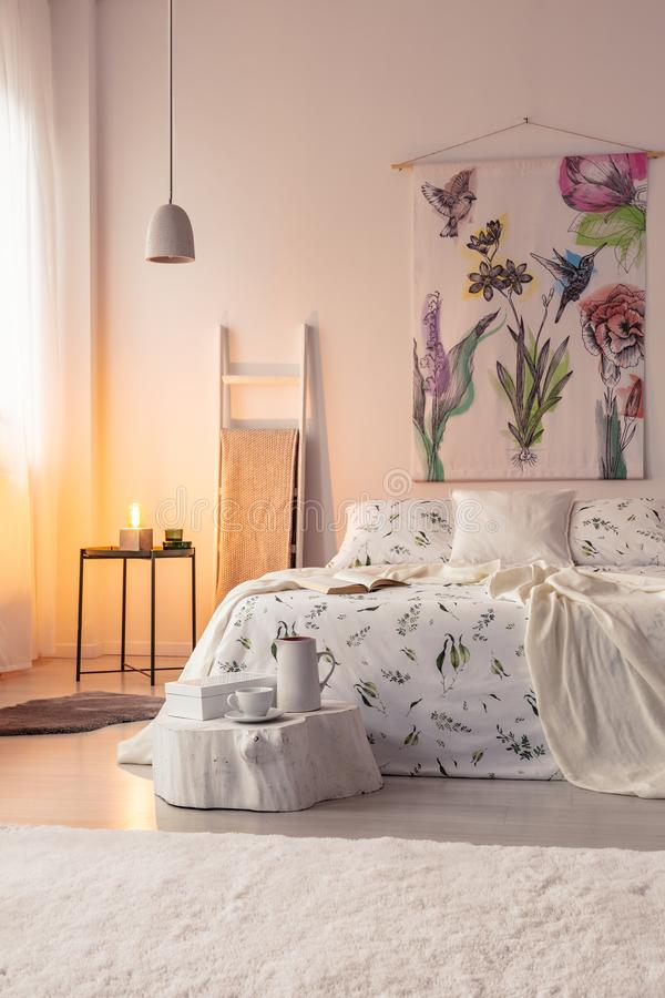 在村庄卧室内部的橙色夜灯光与垂悬在床上的墙壁艺术 实际照片 库存图片
