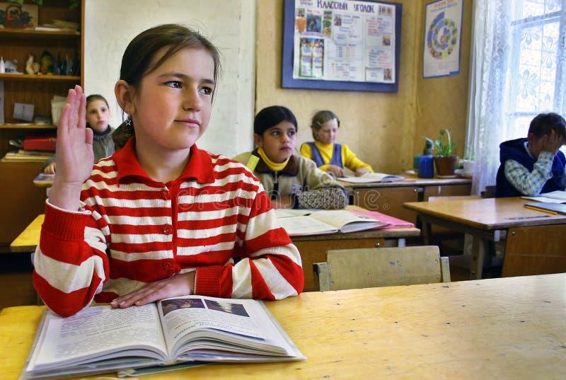 类在村庄学校,女小学生举她的手 库存照片
