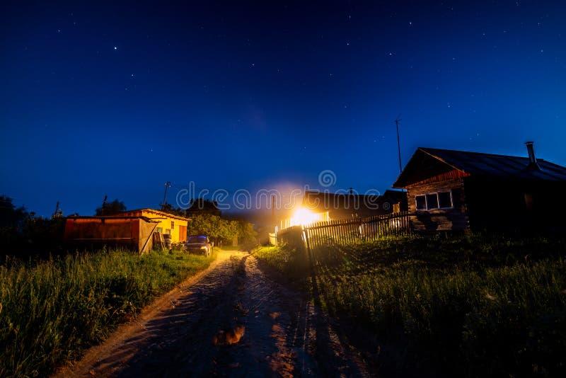在村庄房子的繁星之夜天空在夏天 有一电灯泡光的木房子在入口 ?? 库存图片