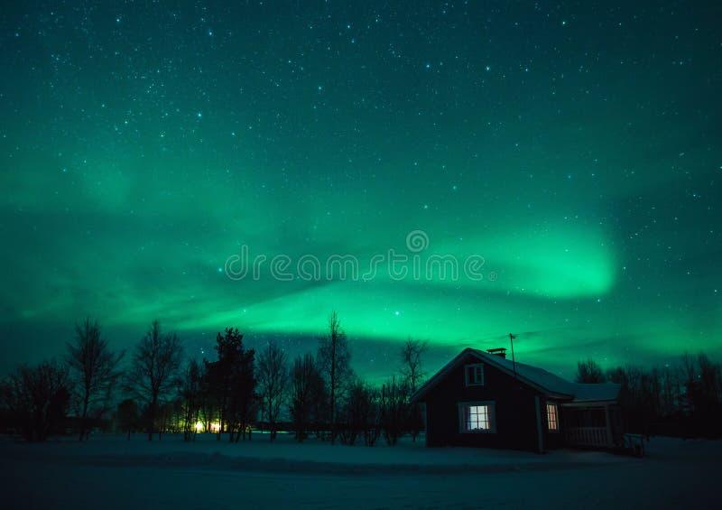 在村庄的北极光极光Borealis在拉普兰村庄 芬兰 免版税库存照片