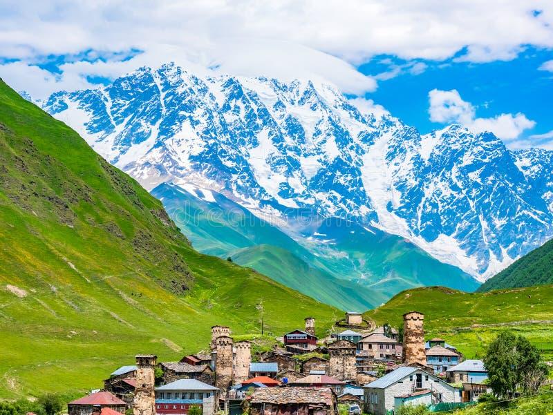 在村庄的美妙的看法反对天空蔚蓝的山的在Svaneti地区,乔治亚 在绿色的传统古老Svan塔 免版税图库摄影