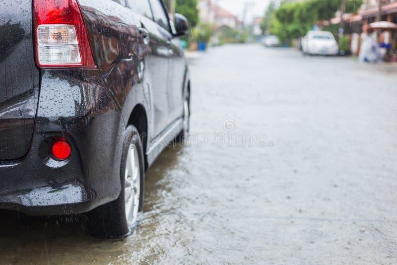 在村庄街道上的汽车停车处,当下雨和展示leve时 免版税图库摄影
