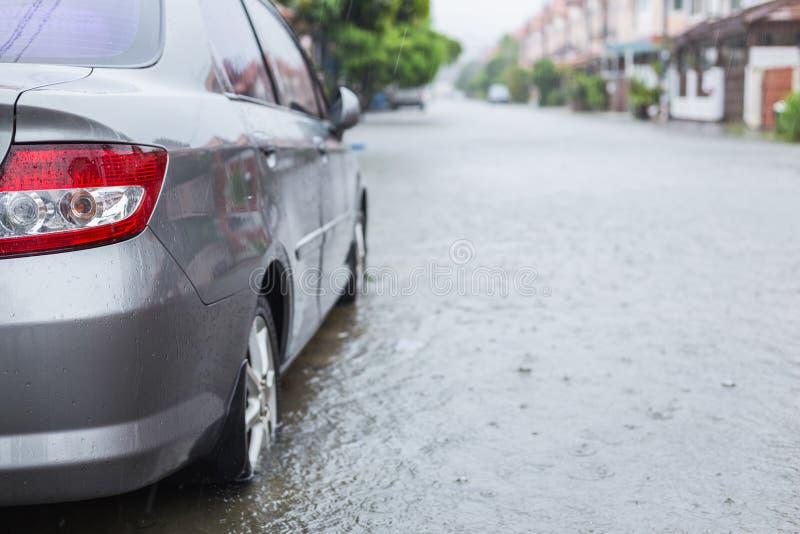 在村庄街道上的汽车停车处,当下雨和展示leve时 免版税库存图片