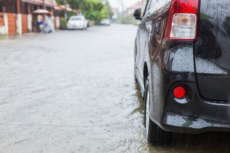 在村庄街道上的汽车停车处,当下雨和展示leve时 库存照片