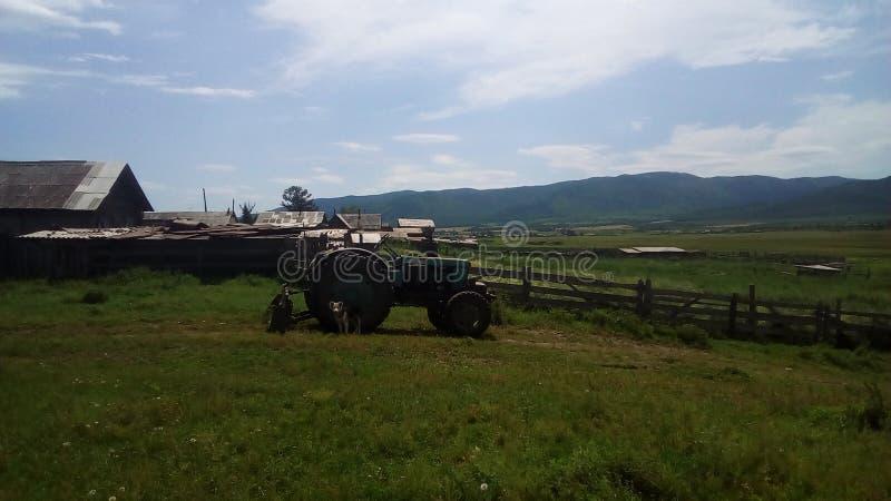 在村庄边缘的拖拉机 免版税库存照片